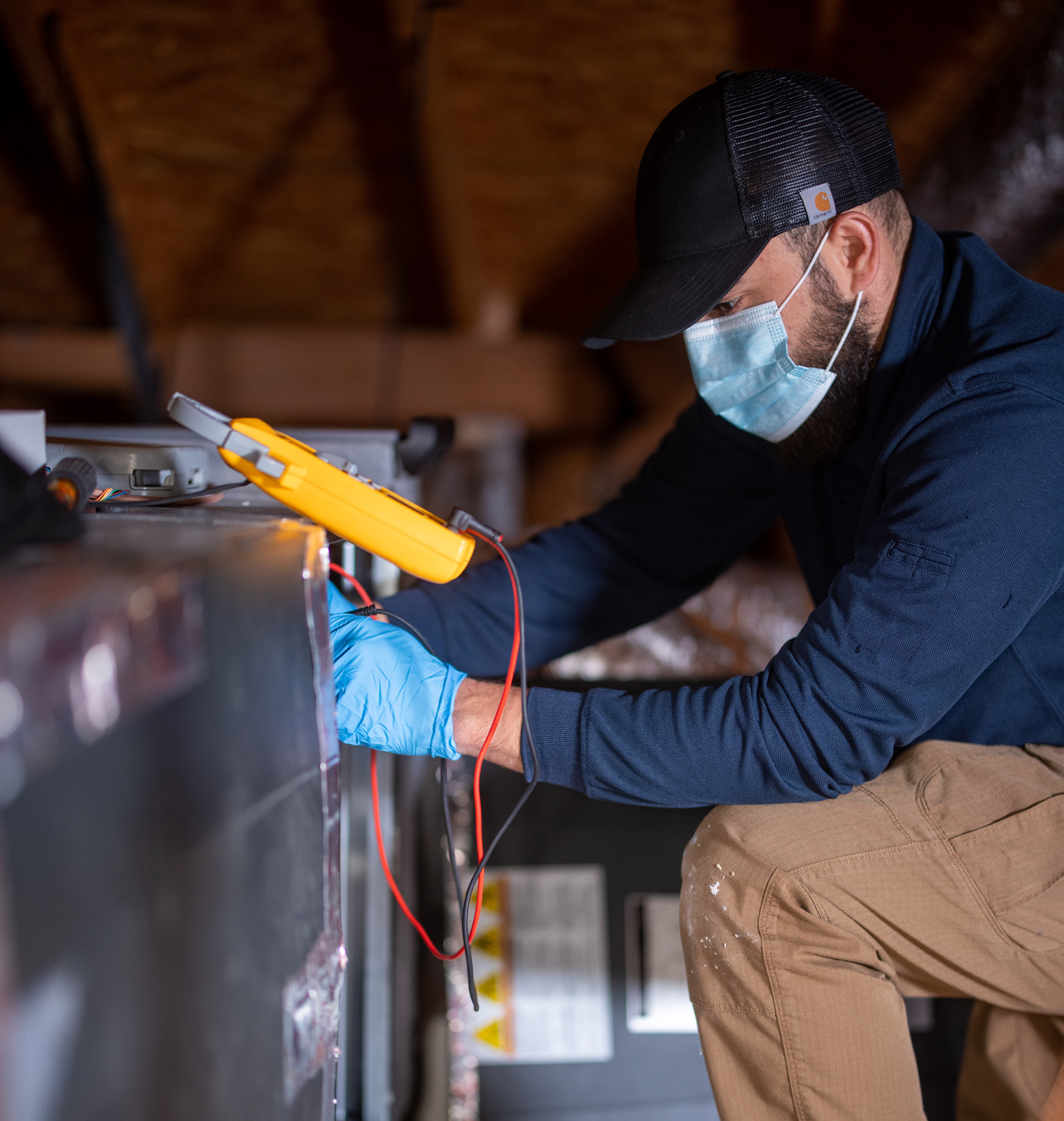 heater reapir technician in attic testing hvac system