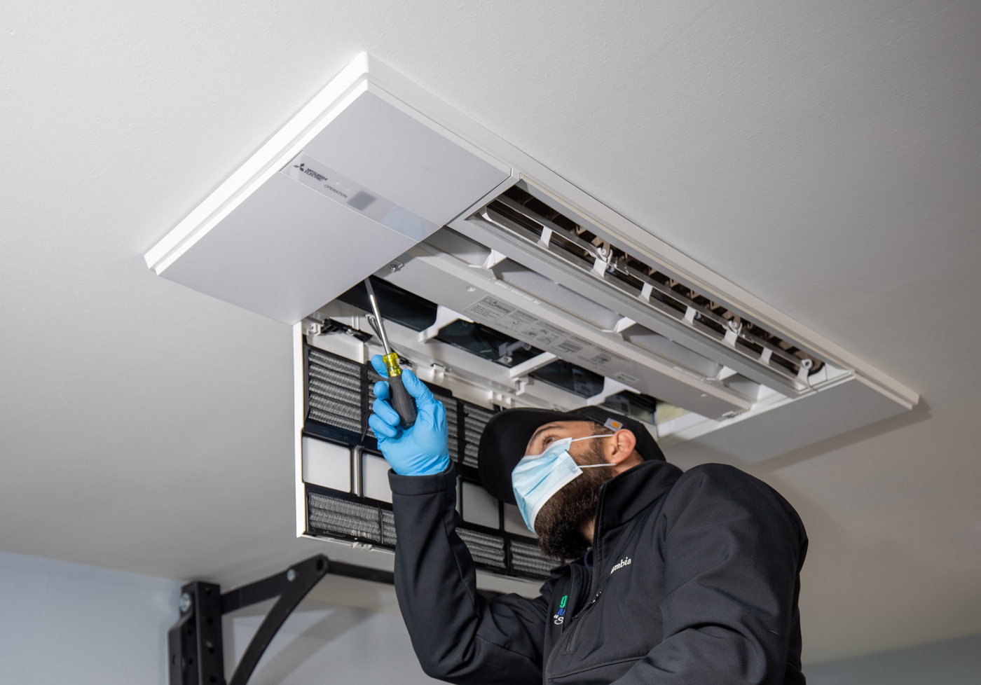 technician installing mini split air conditioning unit in residential garage